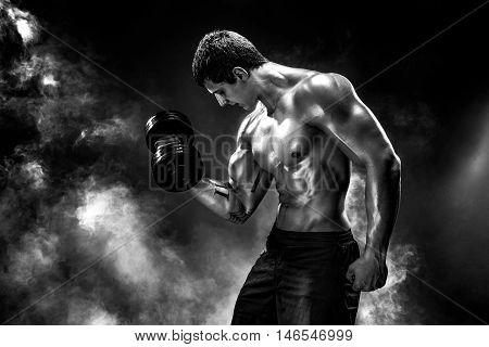 Handsome bodybuilder doing exercise on biceps with dumbbell. Studio shot. Smoke.