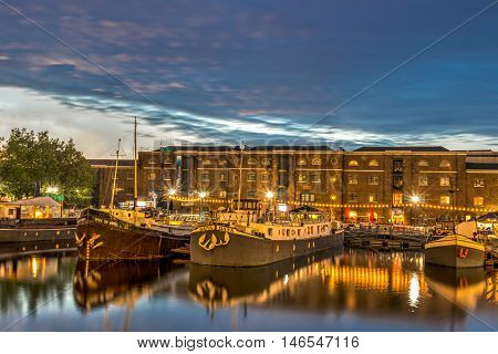 London United Kingdom - July 23 2016: Beautifully lit boats in West India Quay in front of historical warehouse in HDR