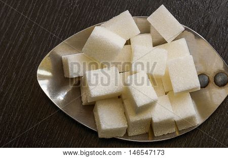 Lumbs of sugar on an old, flat, large ladle