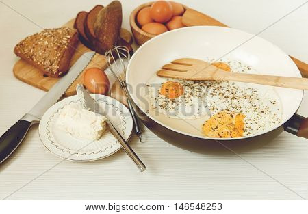 Fried Eggs in the Frying Pan,Breakfast Ingredients.Orange,Bread,Butter.Kitchen Accessories.Cooking Morning Food.Selective Focus