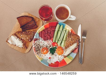 Delicious Breakfast from EggsBread with ButterSausage on the Colorfull Plate.CoffeeRed Juice with White Flowers.Knife and Folk.Brown Background.Top View