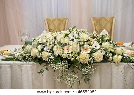 Wedding table decoration. Roses daisies white cream. Floral
