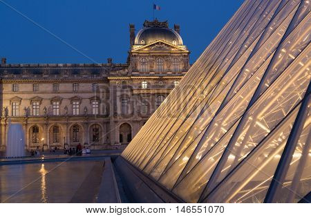 PARIS - AUGUST 15 2016 Louvre museum at twilight in summer. Louvre Museum is one of the world's largest museums every year museum visits more than 8 million visitors.