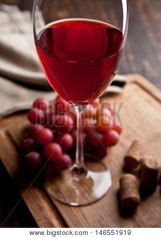 Glass of red wine and grapes on wooden board and corks. Great for bar and restaurant. Still Life Photography