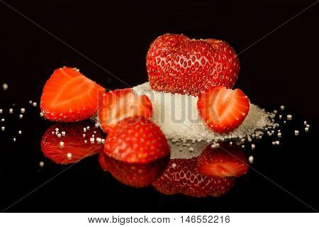 strawberry and slices on sugar on a reflecting surface