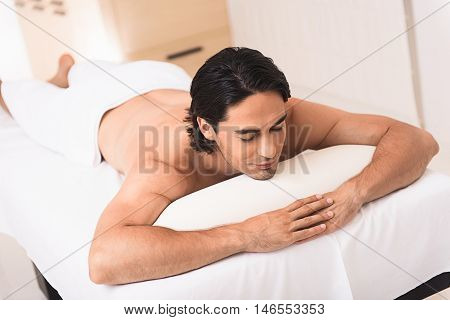 top view of poise secluded man in spa salon, lying on a massage table under the towel