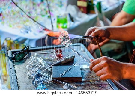Glass blowing process with two hands on table.