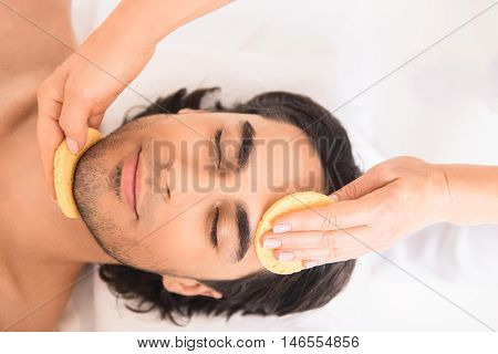 Relaxed young man is getting facial treatment at spa. He is lying and gently smiling. Female arms are touching sponge to his chin and forehead