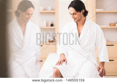 Happy young man is relaxing at wellness center. He is sitting on massage table in white bathrobe and smiling