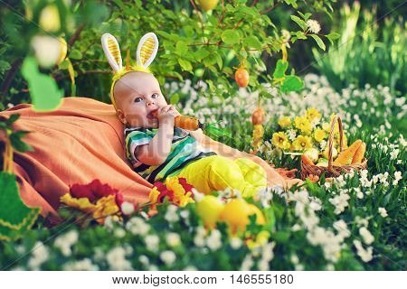 Baby in the Bunny suit bites a carrot. Easter decor