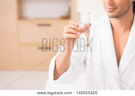 Carefree young guy is resting aster spa procedure. He is holding glass of water and smiling. Guy is sitting in white bathrobe