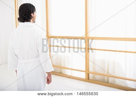 Young guy is resting in bathrobe at spa. He is standing and looking at window pensively. Focus on his back