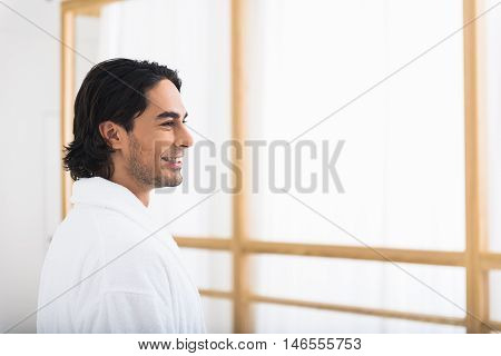 Carefree guy is relaxing in bathrobe at home. He is looking at window and dreaming. Guy is smiling happily
