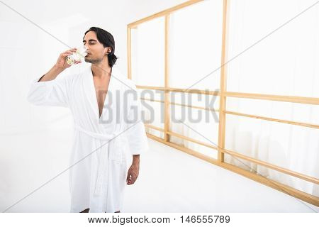 Young man is drinking lemonade after spa procedure. He is standing in bathrobe and relaxing. His eyes are closed with pleasure