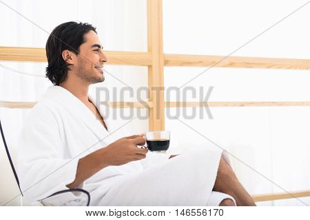 Happy young man is drinking coffee in morning. He is sitting on chair with relaxation and smiling. Man is wearing white bathrobe