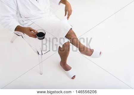 Close up of male body sitting on chair with relaxation. Man in bathrobe is holding cup of coffee
