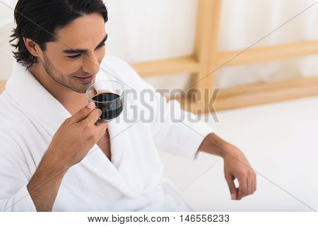 Carefree young man is drinking coffee on vacation. He is sitting in bathrobe and smiling