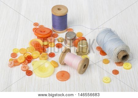 Different thread spools with colorful buttons and thimbles on light surface.