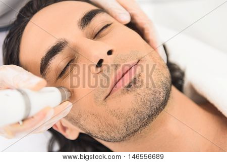 Close up of male face getting electroporation massage therapy by cosmetologist