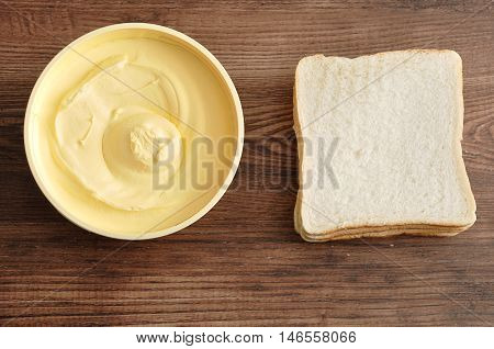 Butter and bread isolated on a wooden background