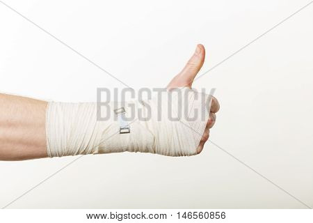 Good news and information. Medicine aspects. Male hand with bandage showing thumb up sign symbol.