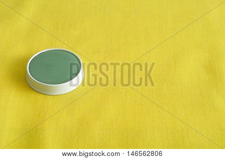 A green ointment in a white tin isolated on a yellow background