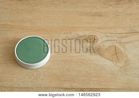 A green ointment in a white tin isolated on a wooden background