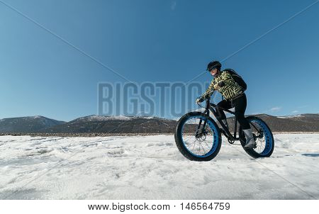 Fatbike (also called fat bike or fat-tire bike) - Cycling on large wheels. Extreme girl riding a bike on snow melted ice. The Lake Baikal.