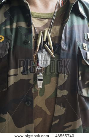 NEW YORK MAY 30 2016: Close on dog tags and bullet casings on a necklace worn by a US veteran at the Memorial Day Observance service on the Intrepid Sea Air & Space Museum during Fleet Week NY 2016.