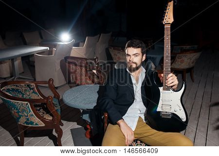 guitarist with electric guitar; hipster with amp sitting in chair;