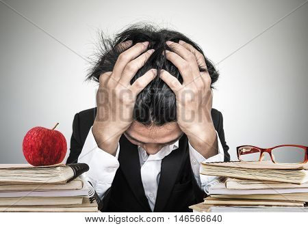 Businessman or business student overworked, stress out, with piles of book and notebook with apple with eye glasses