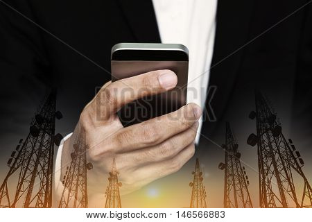Businessman using mobile phone with multi exposure Telecommunication towers with TV antennas and satellite dish in sunset