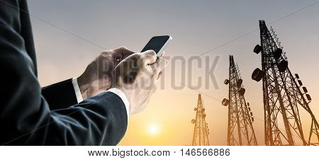 Businessman using mobile phone with Telecommunication towers with TV antennas and satellite dish in sunset