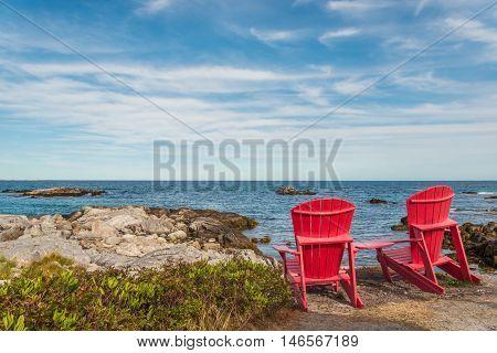 Red chairs facing Keji Seaside beach (South Shore Nova Scotia Canada)