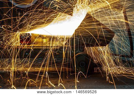 worker with sparkle welding metal in a car factory