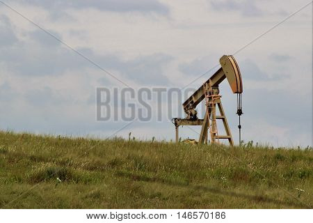 oil rig on the Kansas prairie against a cloud filled sky