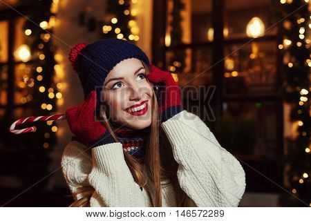 Night street portrait of smiling beautiful young woman speaking on mobile phone and looking up. Lady wearing classic winter knitted clothes. Festive Christmas garland lights. Close up. Toned