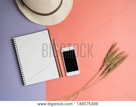 Top view of open spiral notebook brown pencil mobile phone dried grass flower and white hat on two tone pastel violet and orange background