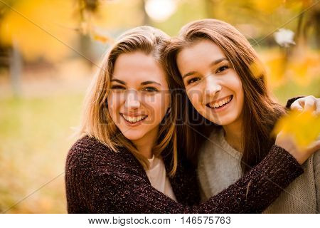 Portrait of two friends embracing -  teenager girls outdoor in autumn
