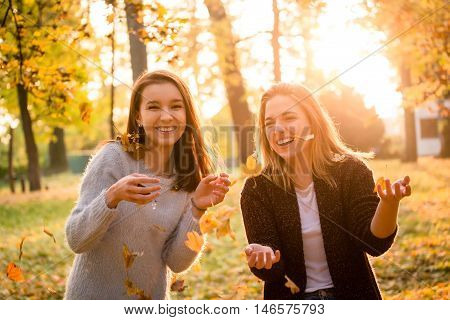 Two friends throwing leaves and having fun outdoor in autumn nature at sunset