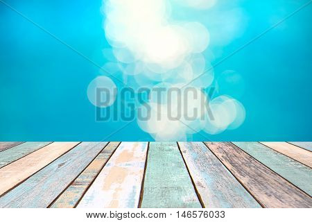 Perspective wood table top and blurry blue water bokeh abstract background product display montage