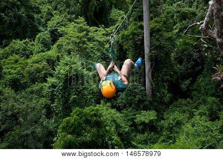 A woman having fun doing extreme sport zip line