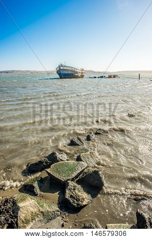 An old neglected wooden fishing boat lies tied up with ropes in the shallow waters in a bay by Luderitz near the rocky shore.