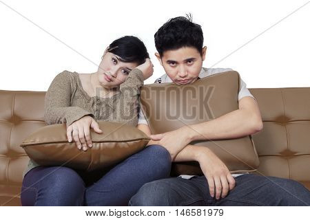 Portrait of two boring couple sitting on the sofa while looking at the camera