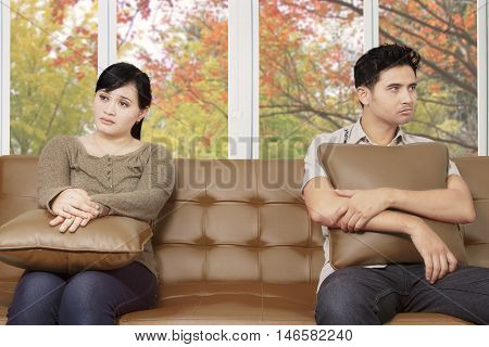 Two young unhappy couple sitting on the sofa and looks having problems in relationship shot at home