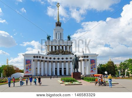 MOSCOW RUSSIA - JULY 23 2016: Unidentified people walk near main pavilion of Exhibition of Achievements of National Economy and monument to Lenin Moscow