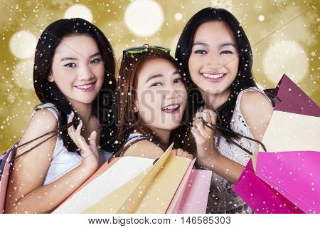 Attractive shopaholics carrying shopping bags and smiling at the camera shot with bokeh background