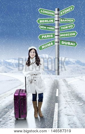Portrait of pretty girl in winter coat standing on the road with destination choices for winter holiday