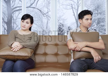 Two unhappy couple having problems and sitting on the couch with winter background on the window at home