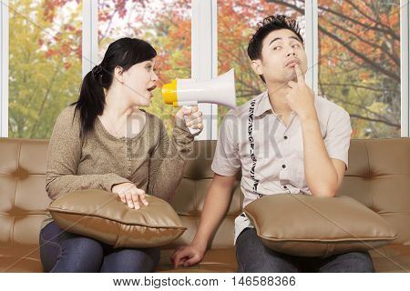 Portrait of a young woman sitting on the sofa while quarreling and screaming at her husband